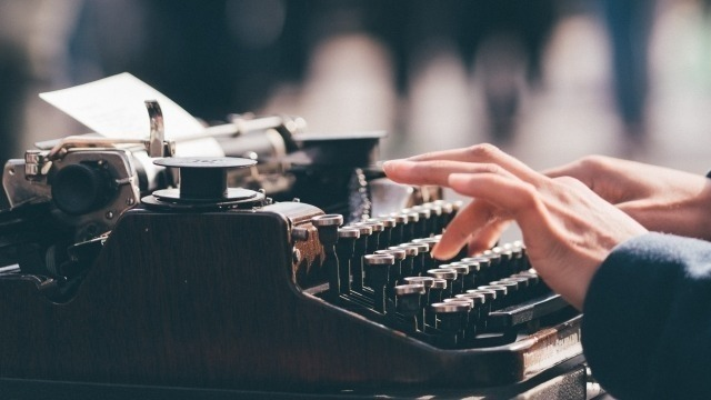 Image of hands typing on old fashioned typewriter