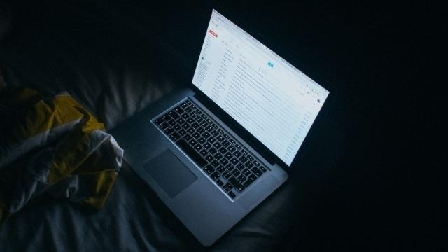 Laptop open in a dark room