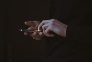 Hands using smart phone.