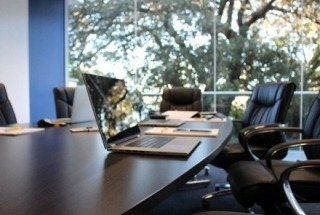 Conference Room table with laptop and notebooks, trees outside